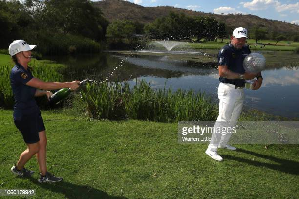 Lee Westwood of England is sprayed with champagne by patrner and caddie Helen Storey after winning the Nedbank Golf Challenge at Gary Player CC on...