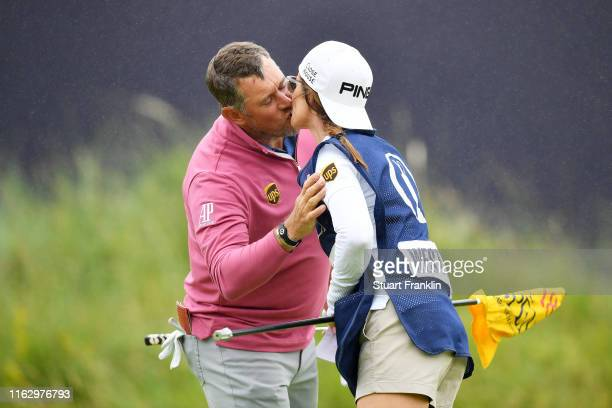 Lee Westwood of England kisses his caddie and girlfriend Helen Storey on the 18th green during the second round of the 148th Open Championship held...