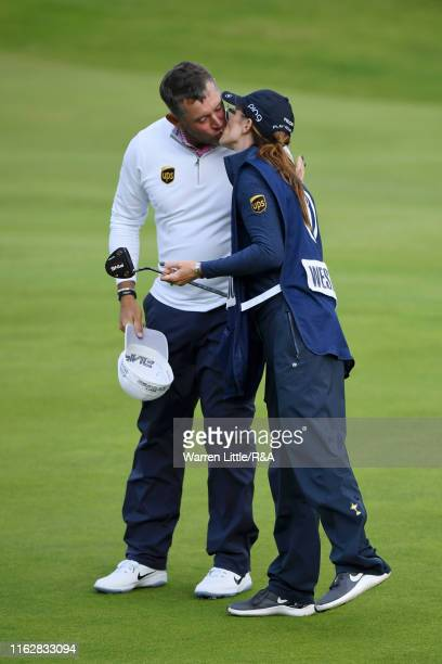Lee Westwood of England kisses his caddy and girlfriend Helen Storey during the first round of the 148th Open Championship held on the Dunluce Links...