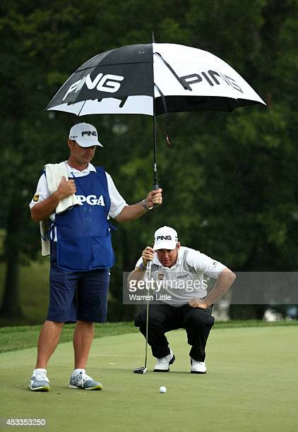 Lee Westwood of England lines up his putt on the 12th green alongside caddie Billy Foster during the second round of the 96th PGA Championship at...
