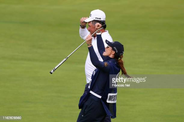 Lee Westwood of England looks on as his caddie Helen Storey celebrates on the 18th green during the first round of the 148th Open Championship held...