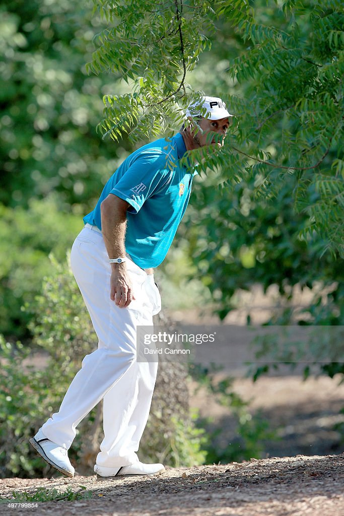 Lee Westwood of England peers through the trees lining up his second shot after a wild tee shot on the first hole during the first round of the 2015 DP World Tour Championship on the Earth Course at Jumeirah Golf Estates on November 19, 2015 in Dubai, United Arab Emirates.