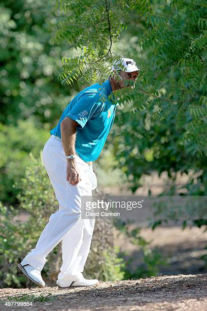 Lee Westwood of England peers through the trees lining up his second shot after a wild tee shot on the first hole during the first round of the 2015...