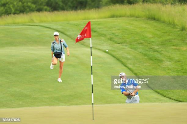 Lee Westwood of England plays a shot on the second hole as his girlfriend Helen Storey looks on during a practice round prior to the 2017 US Open at...