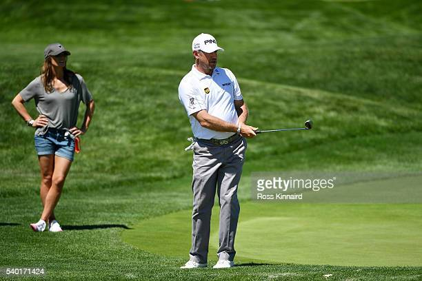 Lee Westwood of England plays his shot as his girlfriend Helen Storey looks on during a practice round prior to the US Open at Oakmont Country Club...