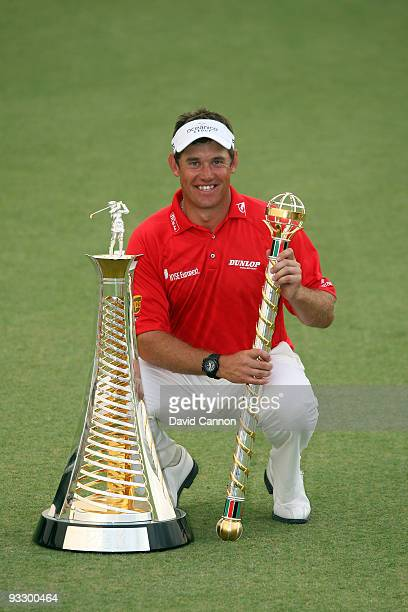 Lee Westwood of England poses with the Dubai World Championship and the Race to Dubai trophies after his victory in the final round of the Dubai...
