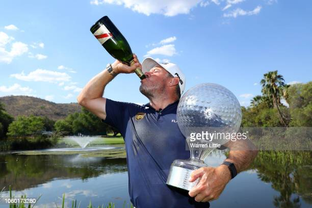 Lee Westwood of England poses with the trophy and drinks champagne after he wins the Nedbank Golf Challenge at Gary Player CC on November 11 2018 in...