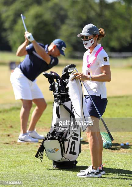 Lee Westwood of England practices as fiancée and caddie, Helen Storey cleans his clubs ahead of the English Championship at Hanbury Manor Marriott...