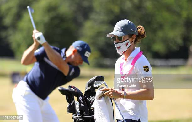 Lee Westwood of England practices on the range as fiancée and caddie, Helen Storey cleans his clubs ahead of the English Championship at Hanbury...