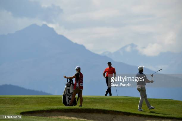 Lee Westwood of England reacts after playing a shot on the seventh as caddie Helen Storey and Rory McIlroy of Northern Ireland look on during Day One...
