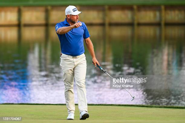 Lee Westwood of England smiles and waves his ball to fans after making a birdie putt on the 17th hole green during the third round of THE PLAYERS...