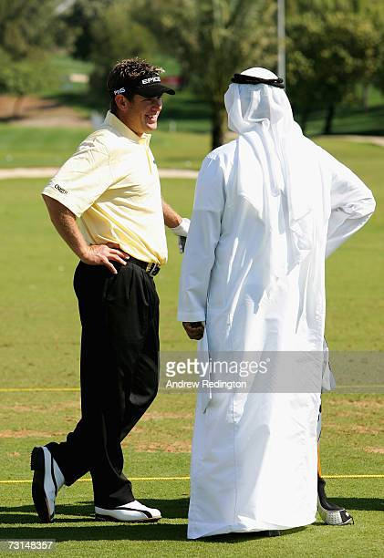 Lee Westwood of England talks with a man wearing local dress during practice for the Dubai Desert Classic on the Majilis Course at Emirates Golf Club...