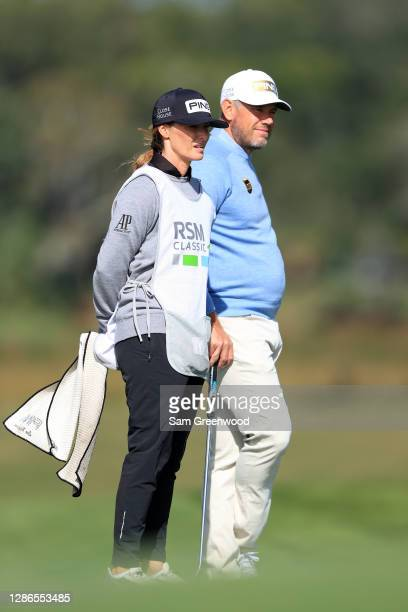Lee Westwood of England waits with caddie Helen Storey on the eighth hole during the first round of The RSM Classic at the Seaside Course at Sea...