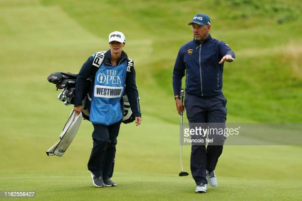 Lee Westwood of England walks down the fairway with his caddie and girlfriend Helen Storey during a practice round prior to the 148th Open...