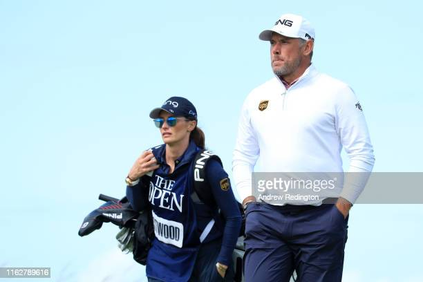 Lee Westwood of England walks down the fairway with his caddie and girlfriend Helen Storey during the first round of the 148th Open Championship held...
