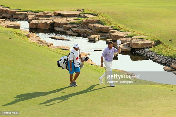 Lee Westwood of England walks up the 18th hole with caddie Ken Herring during day one of the DP World Tour Championship at Jumeirah Golf Estates on...