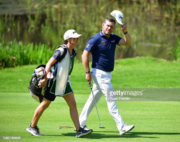Lee Westwood of England waves his cap to acknowledge the fans as he walks with his girlfriend Helen Storey on the 18th hole during the final round of...