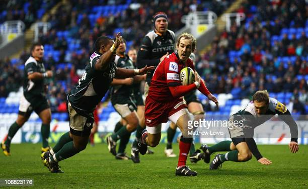 Lee Wiliams of the Scarlets breaks through the defence of Steffon Armitage of London Irish to score a try during the LV Anglo Welsh Cup match between...