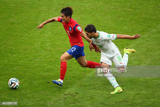 Lee Yong of South Korea dribbles past Abdelmoumene Djabou of Algeria during the 2014 FIFA World Cup Brazil Group H match between South Korea and...