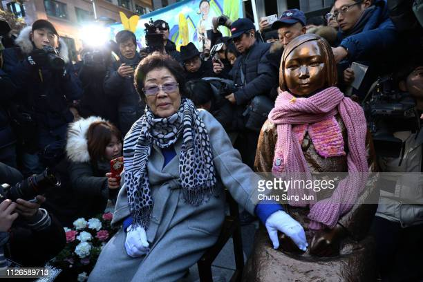 Lee Yong-Soo, a former 'comfort woman,' who served as a sex slave for Japanese troops during World War II, sits next to a comfort woman statue during...