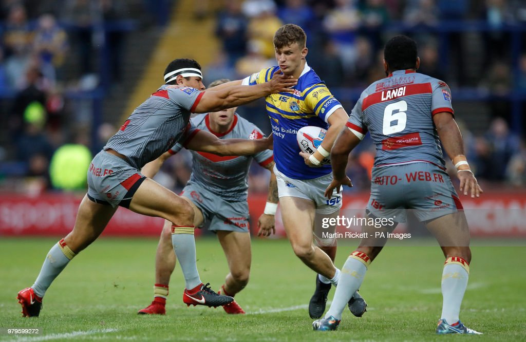 Leeds Rhinos' Ash Handley is tackled by Catalans Dragons' David Mead (left) and Samisoni Langi (right) during the Betfred Super League match at Emerald Headingley Stadium, Leeds.