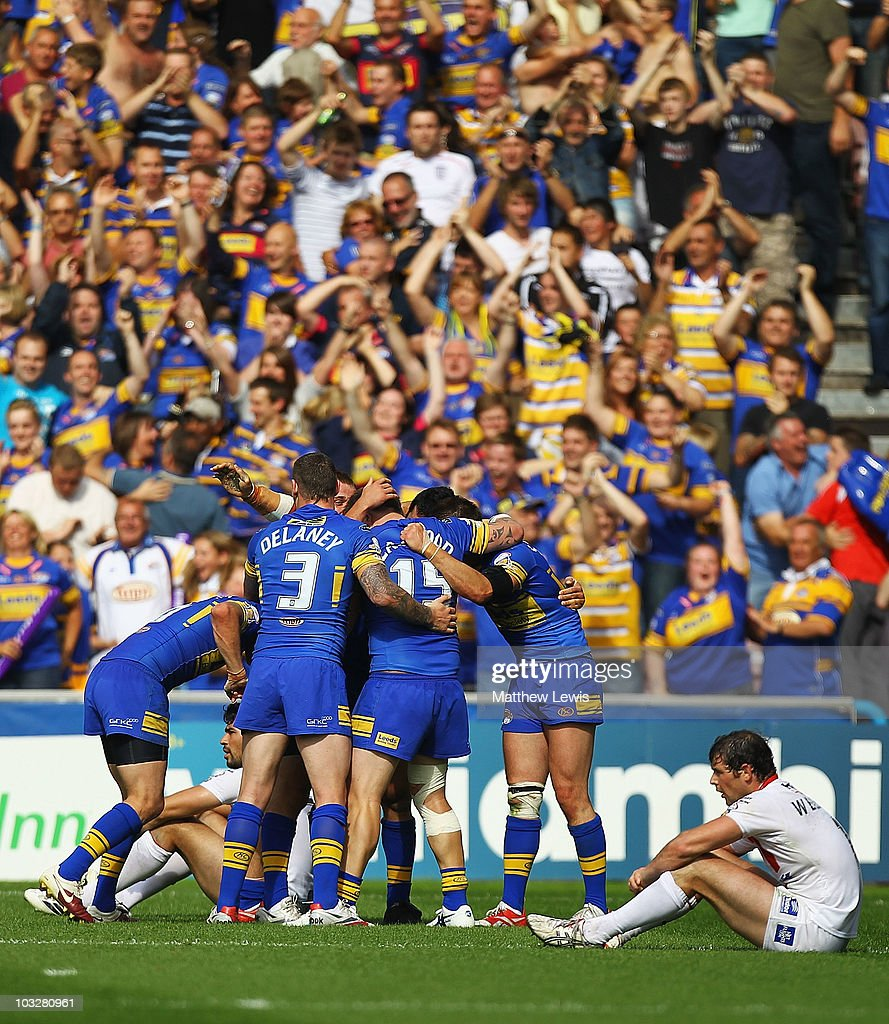 Leeds Rhinos celebrate their teams win, as Paul Wellens of St Helens looks on during the Carnegie Challenge Cup Semi Final match between Leeds Rhinos and St. Helens at the Galpharm Stadium on August 7, 2010 in Huddersfield, England.
