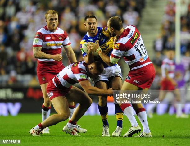 Leeds Rhinos' Mitch Achurch is tackled by Wigan Warriors' Jack Hughes and Lee Mossop during the Super League SemiFinal match at the DW Stadium Wigan