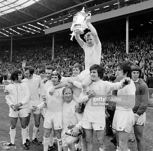 Leeds United captain Billy Bremner holds aloft the trophy as he sits on the shoulders of teammates Allan Clarke and Peter Lorimer after the Leeds...