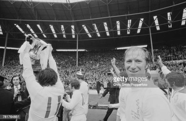 Leeds United defender Jack Charlton grins as his team mate Eddie Gray holds the trophy aloft in front of supporters after Leeds United beat Arsenal...