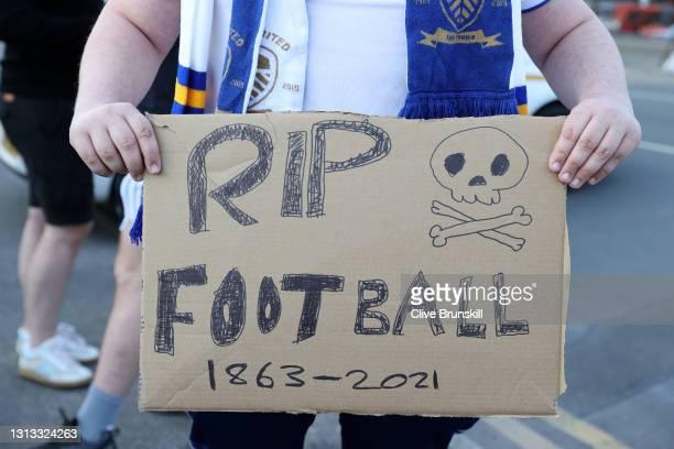 """Leeds United fan holds up a sign reading """"RIP Football 1863-2021"""" in protest to the European Super League outside the stadium prior to the Premier..."""