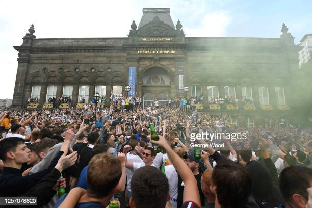 Leeds United fans celebrate after winning the Sky Bet Championship title at Millennium Square on July 19 2020 in Leeds England