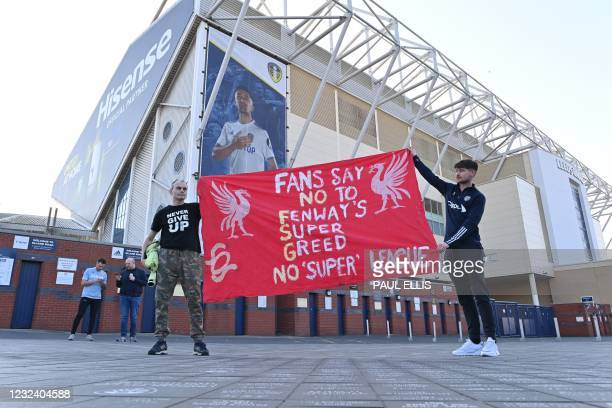 Leeds United fans hold a banner against plans for a European Super League and the involvement of Liverpool football club outside Elland Road ahead of...