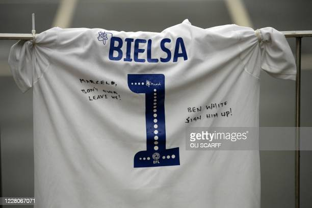 Leeds United football shirt, with the name of Argentinian head coach Marcelo Bielsa, hangs on railings outside the team's Elland Road stadium, in...