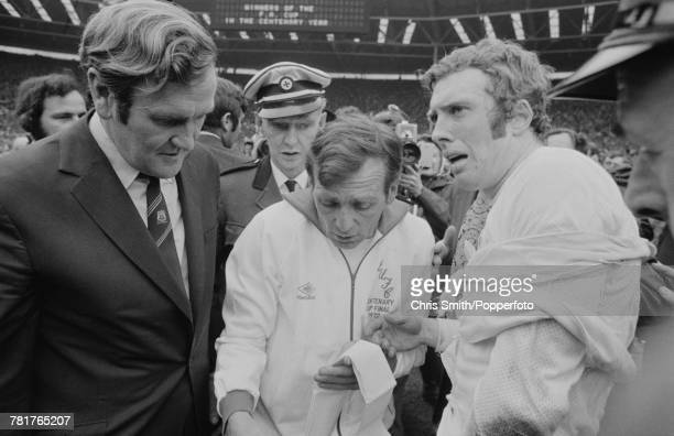 Leeds United forward Mick Jones receives treatment for an injury by club trainer Les Cocker as manager Don Revie looks on after Leeds United beat...