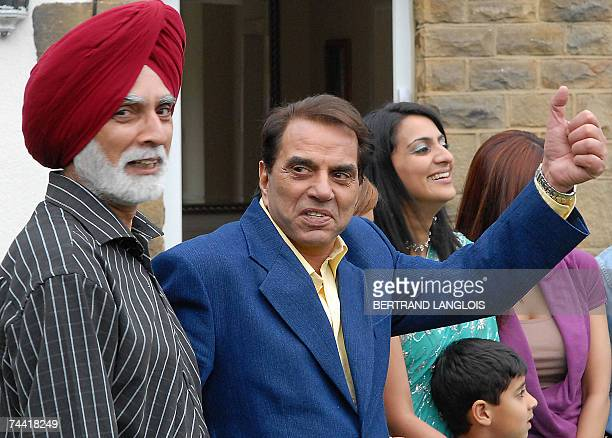 Indian film star Dharmendra Deol gestures as he visits a family in Leeds 06 June 2007 as part of the promotion of the forthcoming film Apne during...