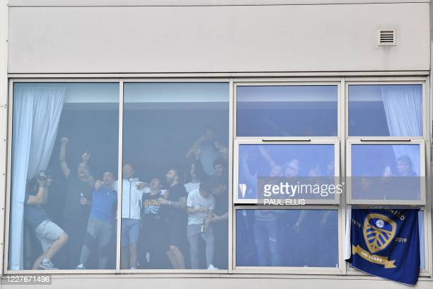 Leeds United players at a window inside the stadium gesture to supporters gathering outside their Elland Road ground to celebrate the club's return...