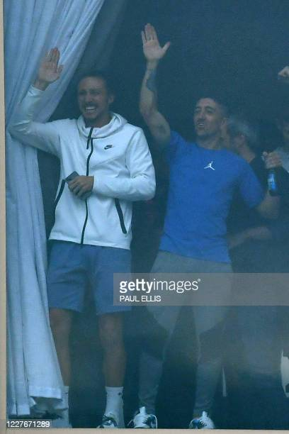Leeds United players Luke Ayling and Pablo Hernandez join teammates at a window inside the stadium gesture to supporters gathering outside their...