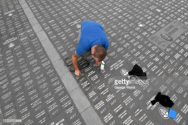 Leeds United supporters Alan Zan and Chris Goodwin clean the Bremner Square memorial stones outside the Leeds United Stadium Elland Road on May 01...