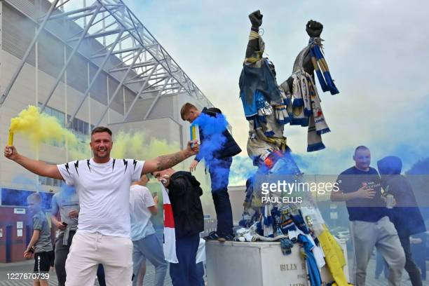 Leeds United supporters gather beside the statue of club legend Billy Bremner outside their Elland Road ground to celebrate the club's return to the...