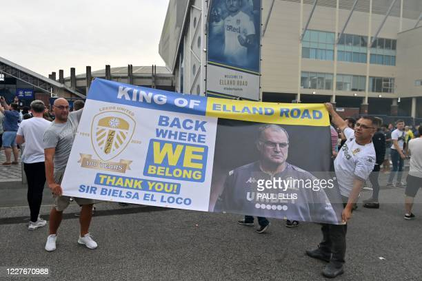 Leeds United supporters hold up a large banner as they gather outside their Elland Road ground to celebrate the club's return to the Premier League...