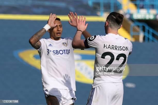 Leeds United's Brazilian midfielder Raphinha Dias Belloli and Leeds United's English midfielder Jack Harrison celebrate the own goal scored by...