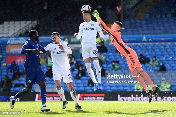 Leeds United's Brazilian-born Spanish striker Rodrigo headers the ball clear as Leeds United's French goalkeeper Illan Meslier jumps to punch it...