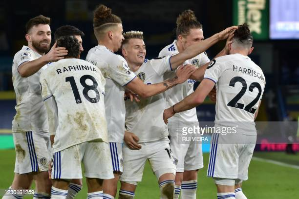 Leeds United's English midfielder Jack Harrison celebrates with teammates after scoring their fifth goal during the English Premier League football...