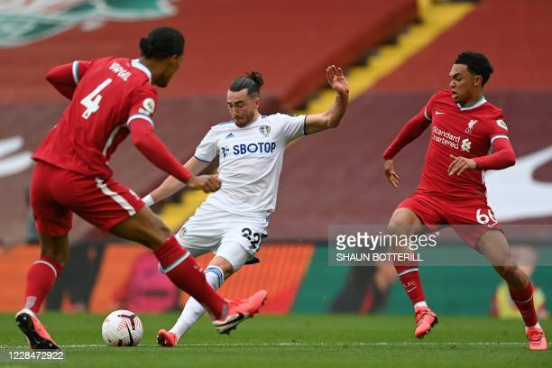 Leeds United's English midfielder Jack Harrison shoots past Liverpool's Dutch defender Virgil van Dijk and Liverpool's English defender Trent...