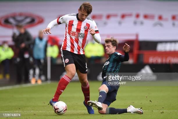 Leeds United's English striker Patrick Bamford tackles Sheffield United's Norwegian midfielder Sander Berge during the English Premier League...
