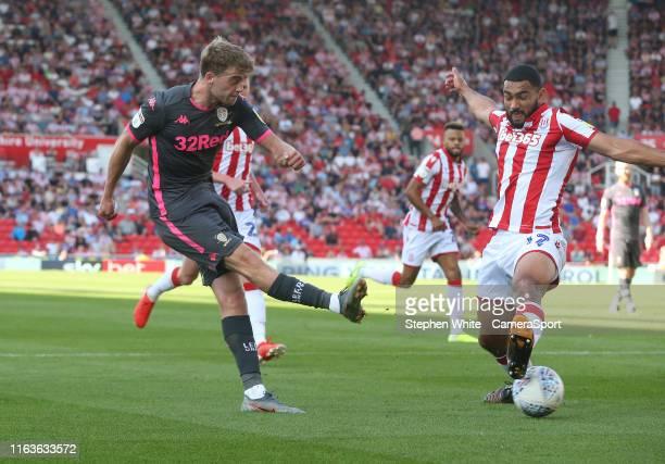 Leeds United's Patrick Bamford crosses the ball for teammate Ezgjan Alioski to score their sides second goal despite the attentions of Stoke City's...