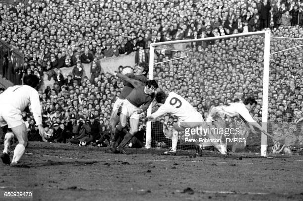 Leeds United's Peter Lorimer looks on as Manchester United's Alex Stepney and Tony Dunne combine to deny Leeds United's Mick Jones and Paul Madeley
