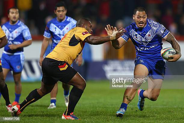 Leeson Ah Mau of Samoa fends off the challenge of Enoch Maki of Papua New Guinea during the Rugby League World Cup Group B match between Papua New...
