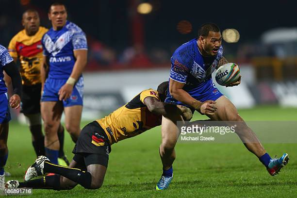 Leeson Ah Mau of Samoa is held up by the challenge of Enoch Maki of Papua New Guinea during the Rugby League World Cup Group B match between Papua...