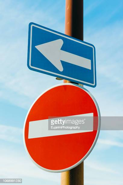 left arrow sign and do not enter sign isolated on blue sky background - wrong way stock pictures, royalty-free photos & images